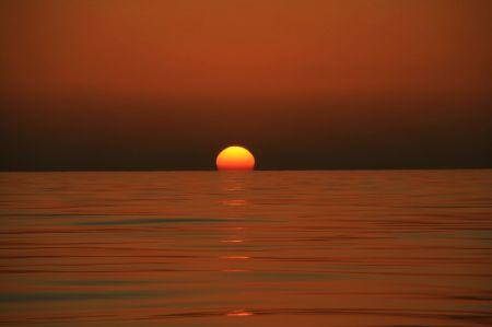Einzig schön an der Windstille - die untergehende Sonne spiegelt sich im ruhigen Meer.