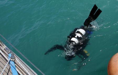 Ein Taucher taucht unter das Boot und spritz eine Lösung in alle Bordauslässe.