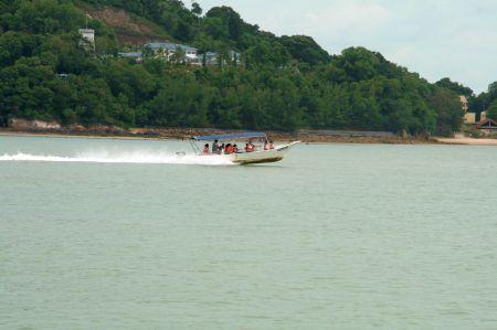 Aus dem Hafen schießt ein kleines Boot voll besetzt mit Kindern.