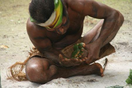 Einer der Männer bespuckt seine Fußsohlen mit einer Masse aus Blättern, die er vorher zerkaut hat.