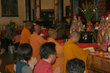 Im Inneren des Tempels knien die Gläubigen hinter den betenden Mönchen.