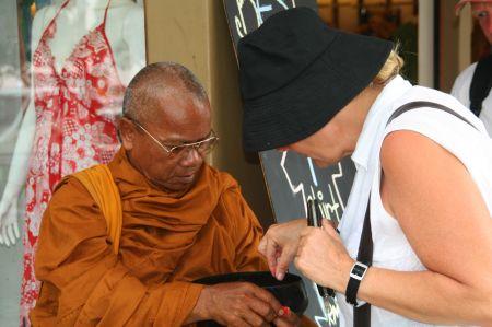 Eva kauft dem freundlichen Mönch an der Straßenecke ein kleines Armband ab.