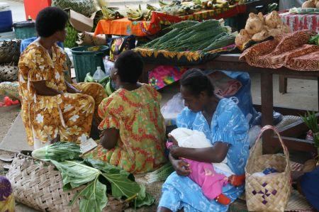 Die Marktfrauen sitzen auf dem Boden bei Ihren Ständen. Die Kinder sind mit dabei.
