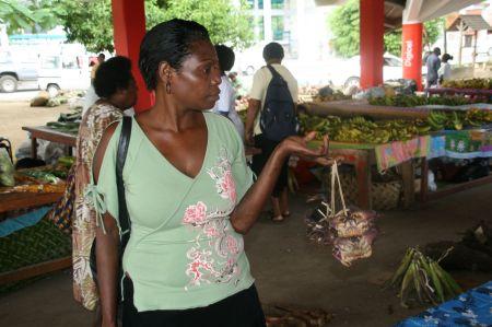 Diese Dame kauft ein Päcken zusammen gebundene Krebse.